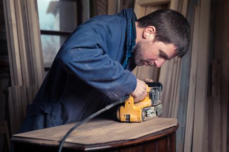 muebles de madera: Retrato de carpintero restauración de muebles de madera vieja con la lijadora de banda en su tienda de madera