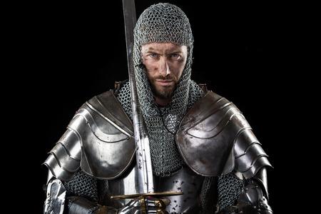 Ritratto di medievale Fronte sporco Warr con l'armatura cotta di maglia e croce rossa spada. Sfondo Scuro Archivio Fotografico - 56532250