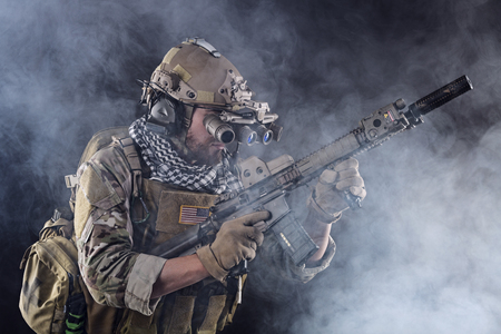 night vision: Portrait of US Army Soldier in Action with Four-eyed night vision goggles in the Smoke; Dark and Foggy Background
