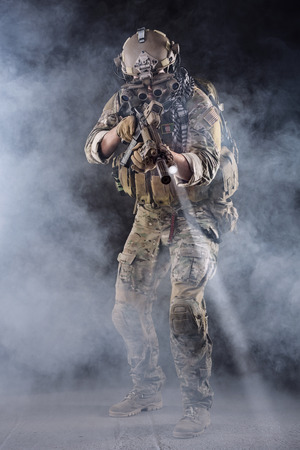 military men: Portrait of US Army Soldier in Action with Four-eyed night vision goggles in the Smoke; Dark and Foggy Background; Beam of light