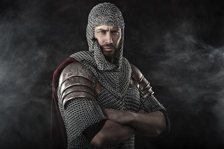 Porträt des mittelalterlichen schmutzigen Gesicht Krieger mit Kettenrüstung. Rauch Wolke auf dunklem Hintergrund