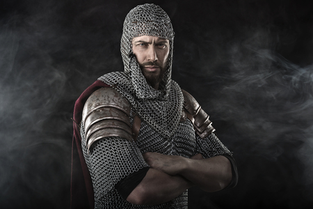 Portrait of Medieval Dirty Face Warrior with chain mail armour. Smoke Cloud on Dark Background