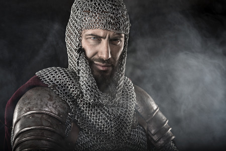 templars: Portrait of Medieval Dirty Face Warrior with chain mail armour. Smoke Cloud on Dark Background