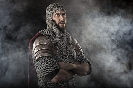 chain armour: Portrait of Medieval Dirty Face Warrior with chain mail armour. Smoke Cloud on Dark Background