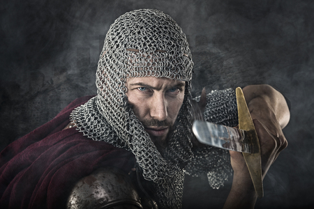 templars: Portrait of Medieval Dirty Face Warrior with chain mail armour and sword. Smoke Cloud on Dark Background
