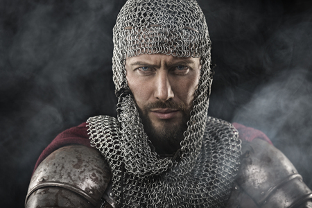 black smoke: Portrait of Medieval Dirty Face Warrior with chain mail armour. Smoke Cloud on Dark Background