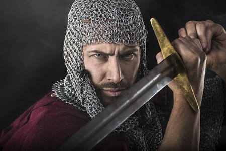 black smoke: Portrait of Medieval Dirty Face Warrior with chain mail armour and sword. Smoke Cloud on Dark Background