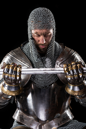 templars: Portrait of Medieval Dirty Face Warrior with chain mail armour and Sword in hands. Black Background