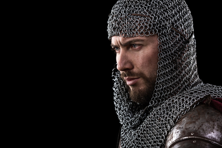 Portrait of Medieval Warrior with chain mail armour and red Cloak. Black Background