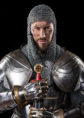 Portrait of Medieval Dirty Face Warrior with chain mail armour and Sword in hands. Black Background