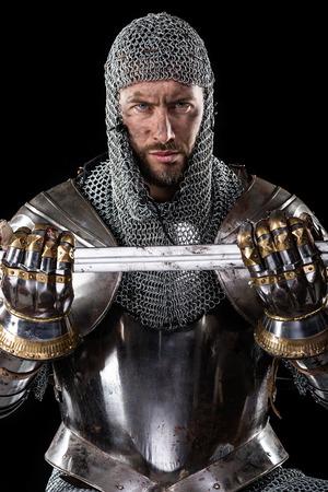 Portret van Middeleeuwse vies gezicht Warr met maliënkolder armor en zwaard in handen. zwarte Achtergrond