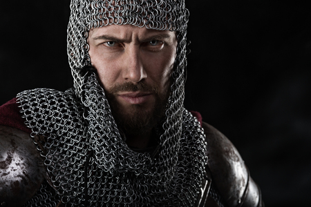 chain armour: Portrait of Medieval Warrior with chain mail armour and red Cloak. Black Background