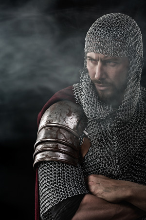 templars: Portrait of Medieval Warrior with chain mail armour and red Cloak. Smoke Cloud on Dark Background