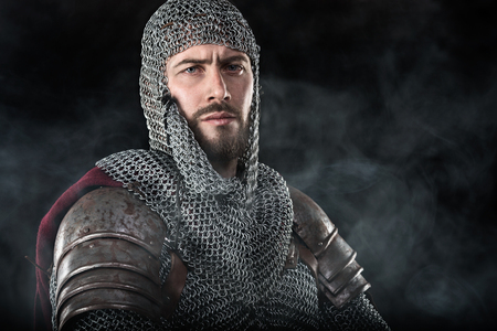 Portrait of Medieval Warrior with chain mail armour and red Cloak. Smoke Cloud on Dark Background