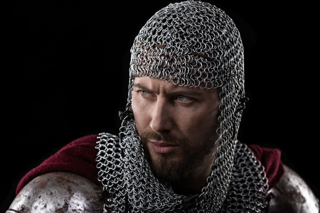 templars: Portrait of Medieval Warrior with chain mail armour and red Cloak. Black Background