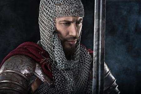 チェーン メールの鎧、剣と赤いマントで中世戦士の肖像画。暗い背景に雲を煙します。