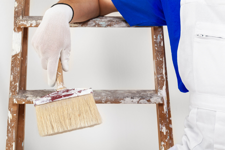 decorating: Close up of painter in white dungarees, gloves and paint brush; wooden ladder Stock Photo