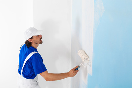 hombre pintando: Vista lateral de pintor con mono blanco y gorra de pintura de una pared con el rodillo de pintura; espacio de la copia
