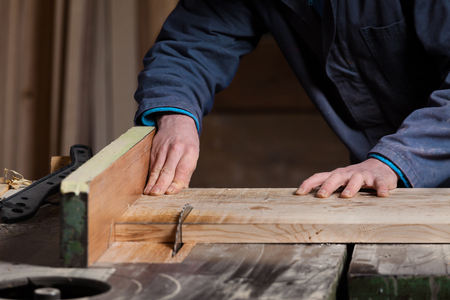 buzz saw: Close up of Carpenters hands cutting wood board with Table Saw in workshop; selective focus