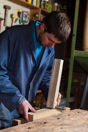 carpenter vise: Portrait of a Carpenter wearing Blue Overalls working on a Wooden planks with a Vise in his Workshop