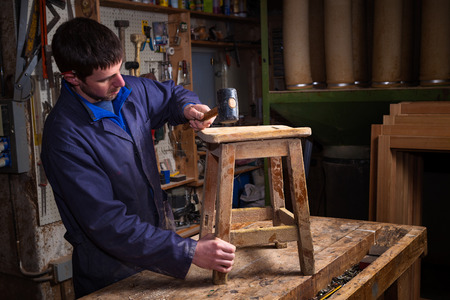 patching: Portrait of Carpenter wearing Blue Overalls restoring Wooden Stool Furniture in his workshop.