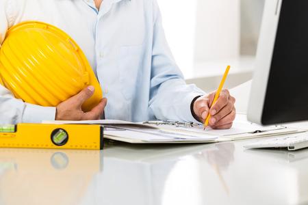 compas de dibujo: Primer plano de las manos del arquitecto el uso de metal Compás de dibujo; Seguridad Casco Amarillo, Plano y herramientas