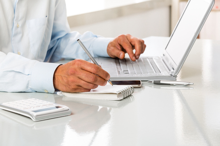 An Unrecognizable man is working by using a laptop computer on white desktop. Hands typing on a keyboard and writing on a blank sheet of notebook