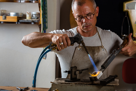 blowtorch: Adult male goldsmith melting and casting precious metal with blowtorch at his Workshop