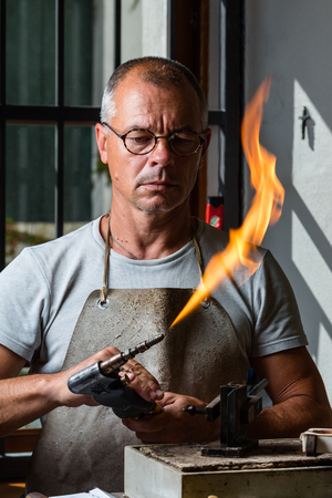 blowtorch: Adult male goldsmith check the blowtorch flame for melting precious metal at his workshop Stock Photo