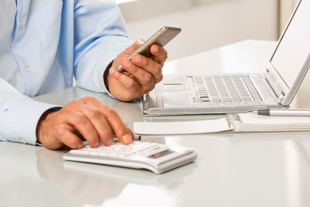 An Unrecognizable man is working by using a phone and calculator on white desktop. Hands typing on calculator Stock Photo