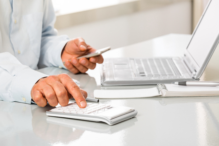 working hands: An Unrecognizable man is working by using a phone and calculator on white desktop. Hands typing on a calculator