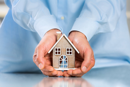 Male hands saving Miniature House on Desktop. Insurance Concept. Insulation Concept Stock Photo