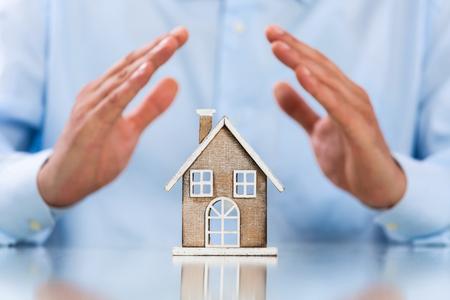 Male hands saving Miniature House on Desktop. Insurance Concept. Insulation Concept Standard-Bild