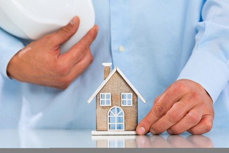 owning: Unrecognizable Contractors Hands showing Miniature House on Desktop. Real Estate Property and Architectural Concept Stock Photo