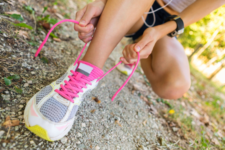 atletismo: Close up of Unrecognizable woman tying shoelaces in the City park.
