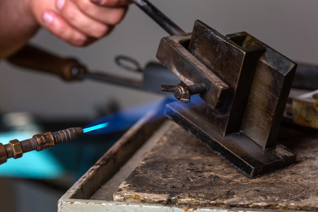 crucible: Close-up of Goldsmith using Blowtorch on Metal Mold in order to melting Metal; Goldsmith Workshop
