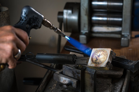 crucible: Close-up of Goldsmith using a Blowtorch on Crucible in order to melting Silver Grains; Goldsmith Workshop;