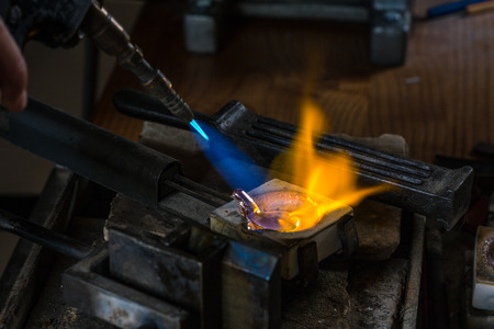 crucible: Melting a Silver Ingot to liquid state in crucible with blowtorch; Goldsmith Workshop; Close-up