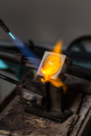 crucible: Close-up of Silver Casting from Crucible to Metal Mold with blowtorch; Goldsmith Workshop;