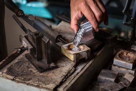 Close-up van de Silver Grains in Crucible voordat ze smelten in vloeibare toestand; Workshop van de goudsmid Stockfoto