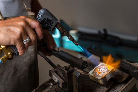 crucible: Close-up of Goldsmith hands melting Silver to liquid state in crucible with blowtorch
