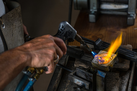 crucible: Close-up of Silver from the Crucible to Metal Casting Mold with blowtorch; Goldsmith Workshop; Stock Photo
