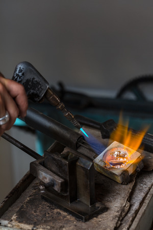 crucible: Melting Silver Grains to liquid state in crucible with blowtorch; Goldsmith Workshop; Close-up