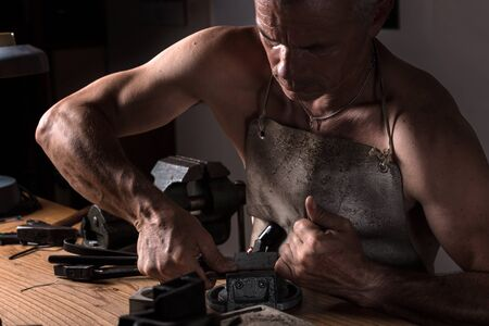 vise: Muscular Middle Aged Artisan working with Metal Vise at his Workshop