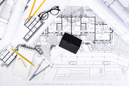 Top View Of Construction Plans With Drawing Tools And House Miniature On Blueprints Architectural