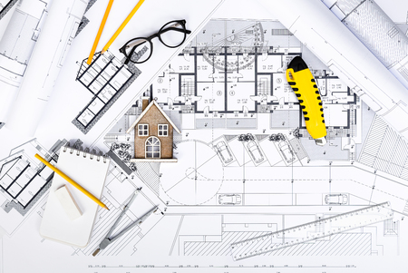 Top View of Construction plans with drawing Tools and House Miniature on blueprints; Architectural and Engineering Housing Concept. Stock Photo