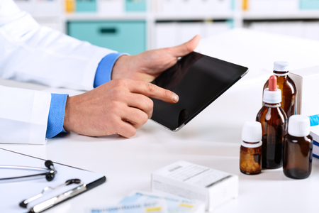 Close up of Doctors hands working on a digital tablet at his Office. Health care, Medical and Pharmacy Concept.