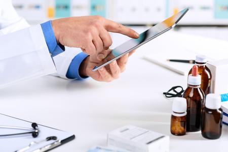 Close-up van de handen van de arts werkt aan een digitale tablet op zijn kantoor. Gezondheidszorg, Medisch en Apotheek Concept.