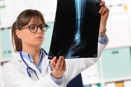 retrato de medio cuerpo de mujer joven médico en bata blanca con estetoscopio mirando radiografía de los pacientes