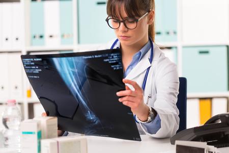 retrato de medio cuerpo de mujer joven médico en bata blanca con estetoscopio mirando radiografía de los pacientes Foto de archivo